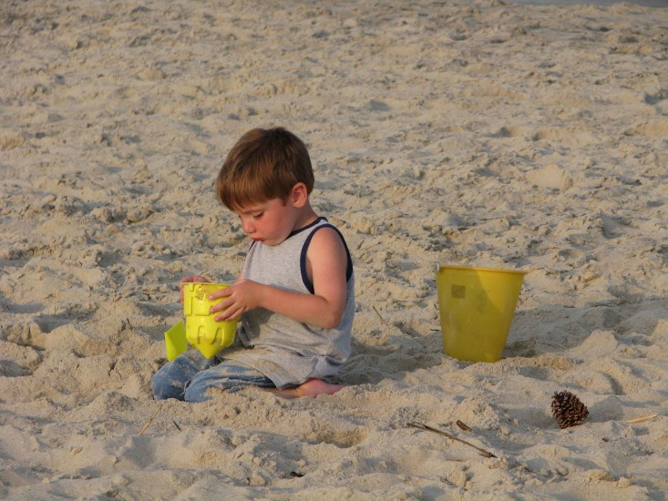 Optimized-young-boy-building-a-sand-castle-at-the-beach