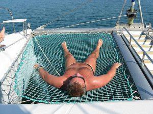 Man on a net of a catamaran